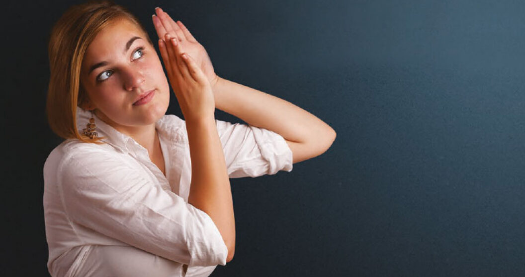 A young woman holds her hands up to her left ear as if to magnify the sounds she hears