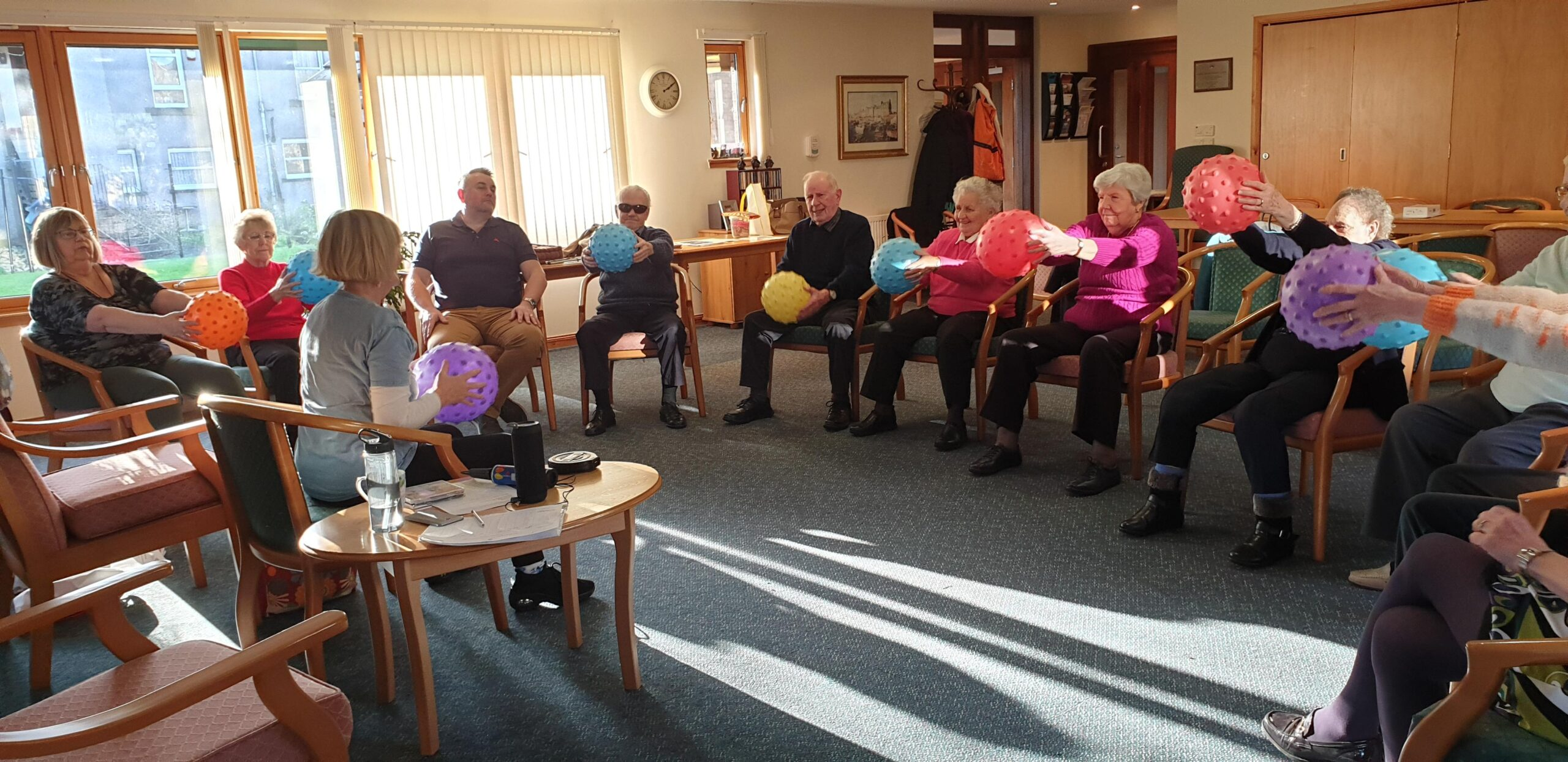 Large group of seated adults doing ball-based exercises
