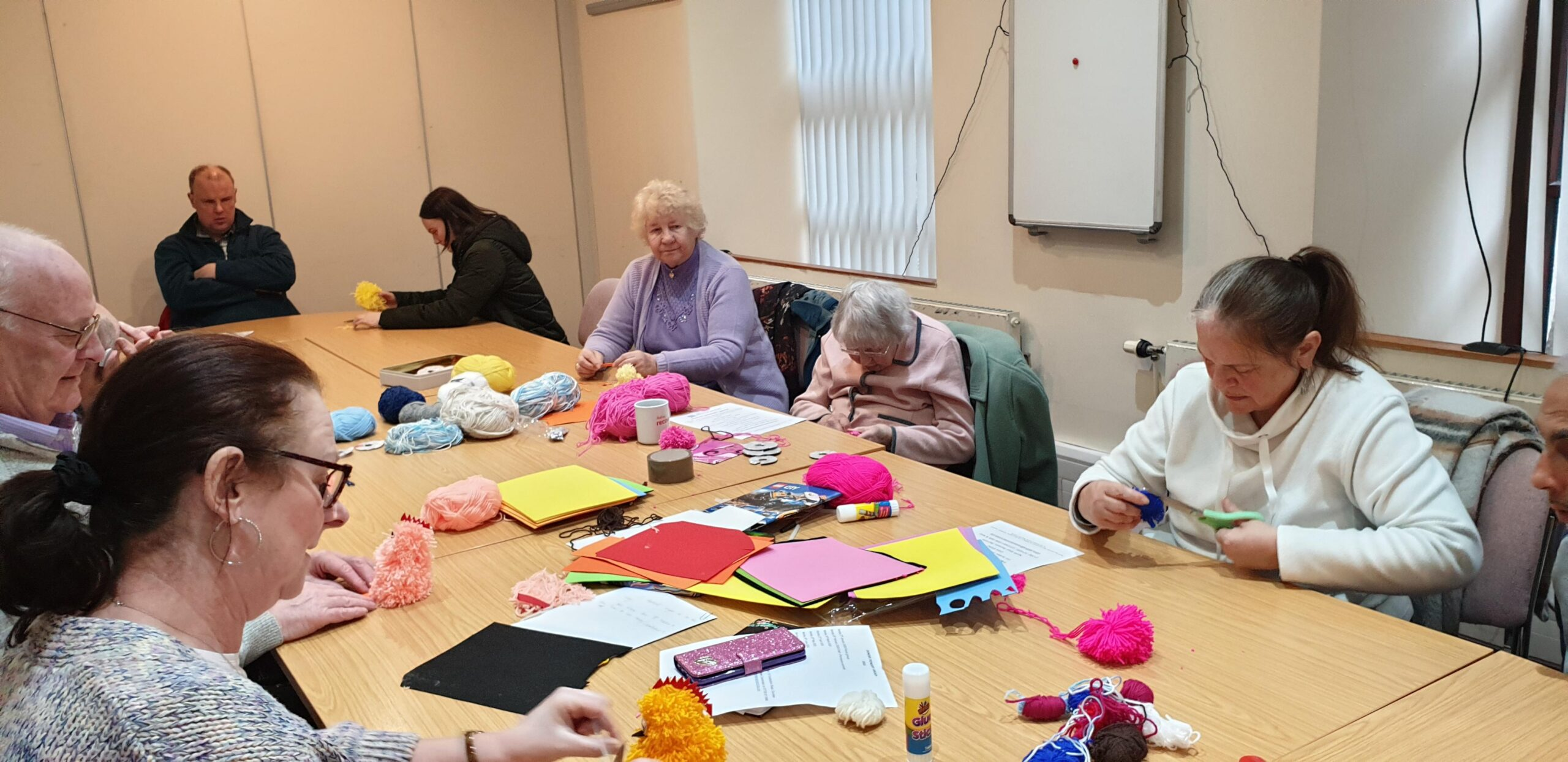 Group of adults sit round table doing crafts