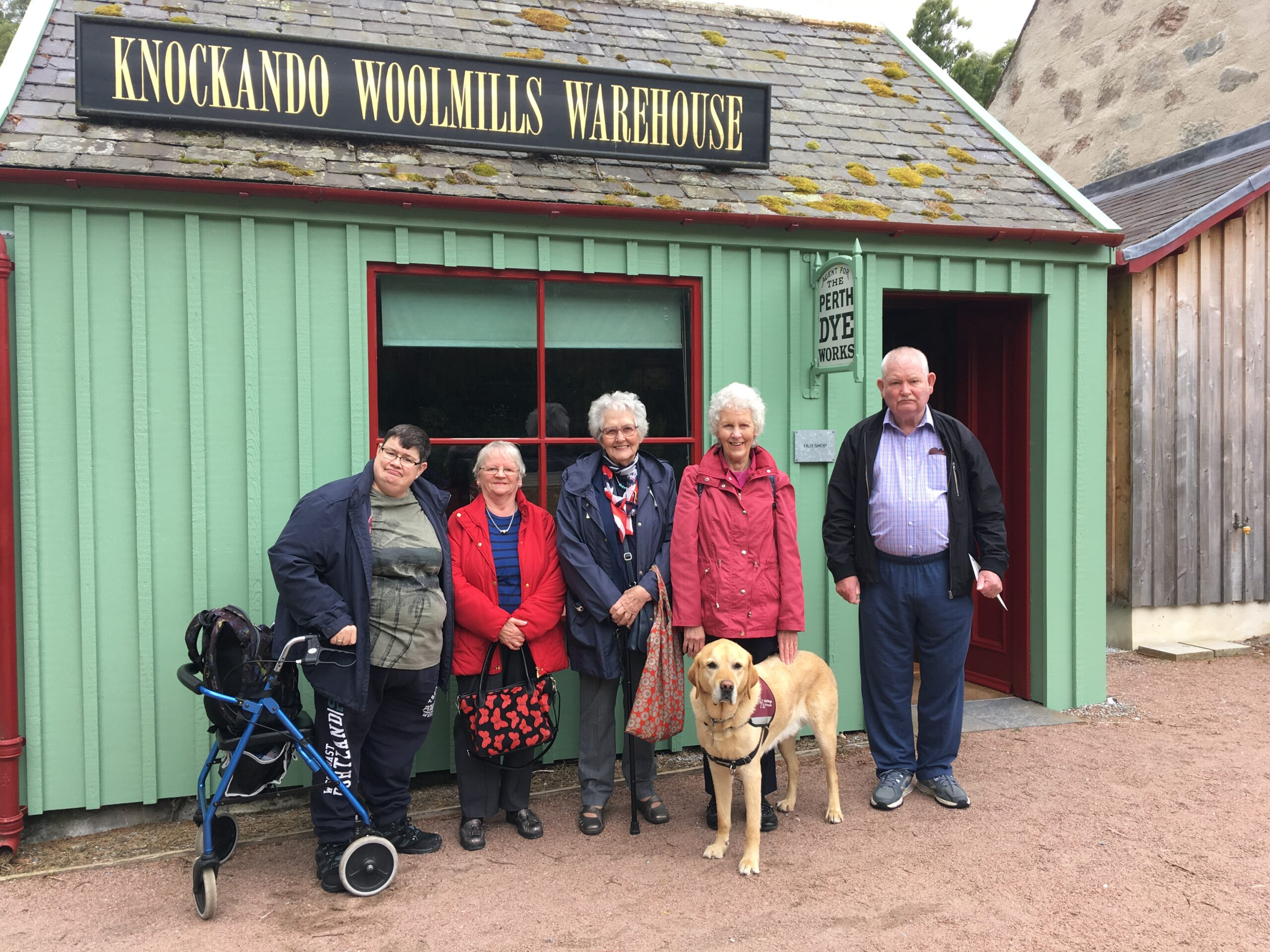 Five adults and a dog stand outside Knockando Woolen Mills