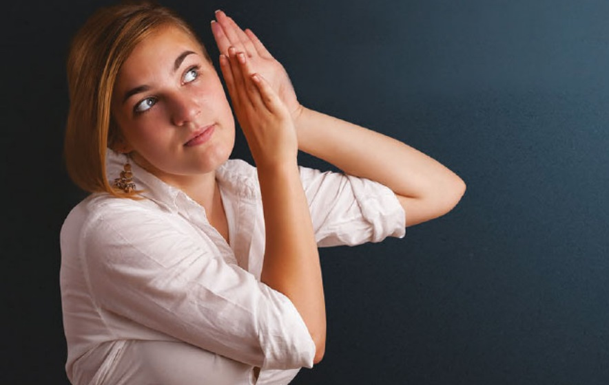 Young woman holds her hands up to her ear to hear what's happening