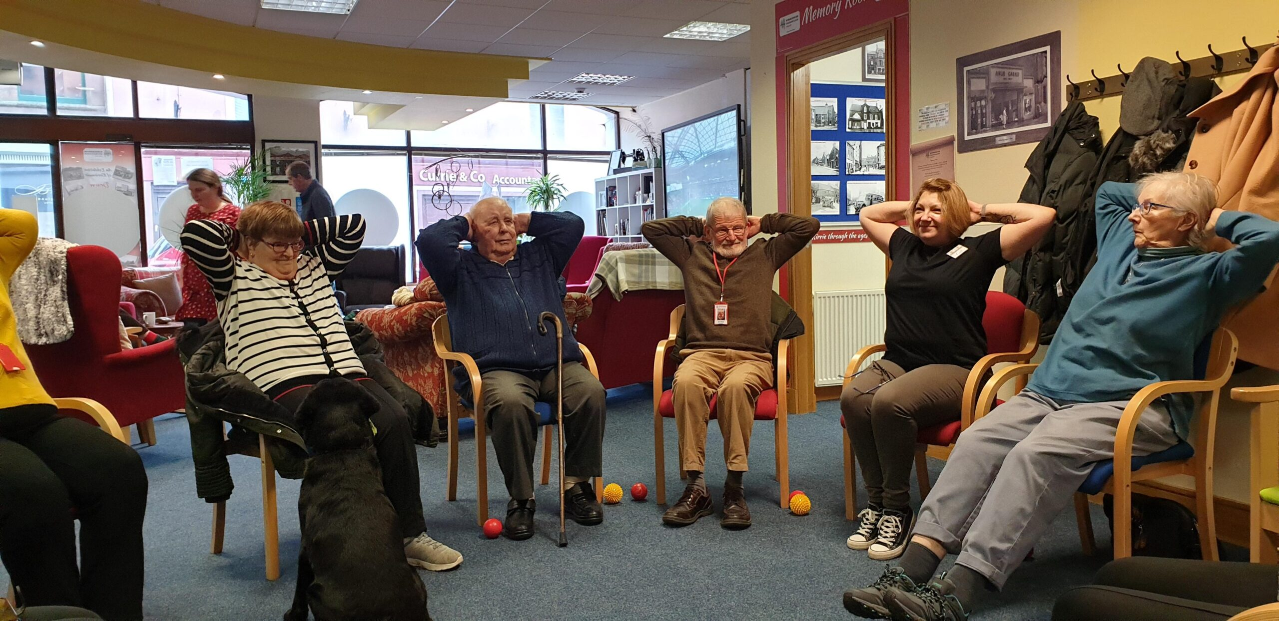 A group of adults take part in a seated excerise group