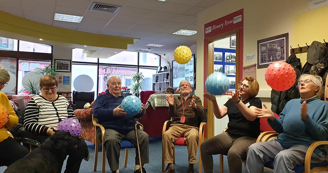 Seated adults doing exercises with balls