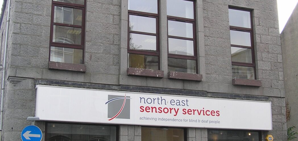 Front elevation of NESS Resource Centre on John Street, in Aberdeen. Large building, with large windows, and NESS sign over the door