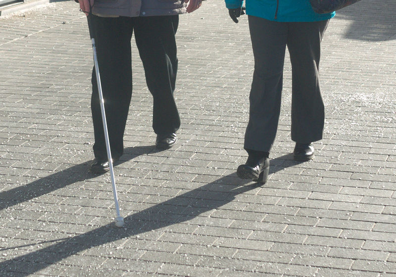 Bottom halves of .two people walking alongside, one using a white long cane.